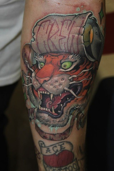 Asian traditional style colored forearm tattoo of tiger head with lettering