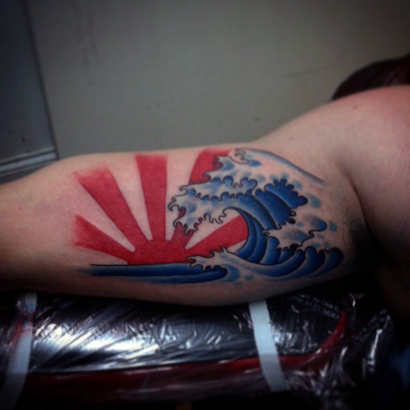 stile asiatico onde grande e sole tatuaggio su braccio