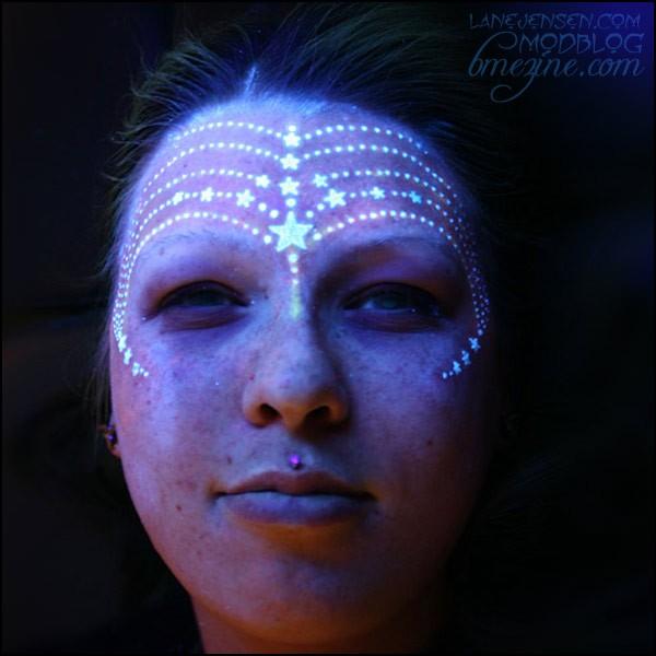 Avatar style black light tattoo on face