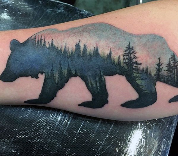 Awesome bear shaped colored tattoo stylized with fores on leg