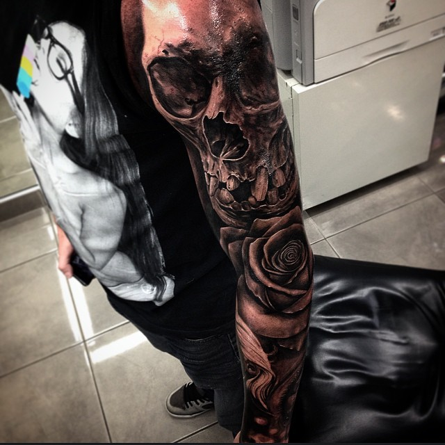 Awesome black and white human skull tattoo on sleeve with big rose