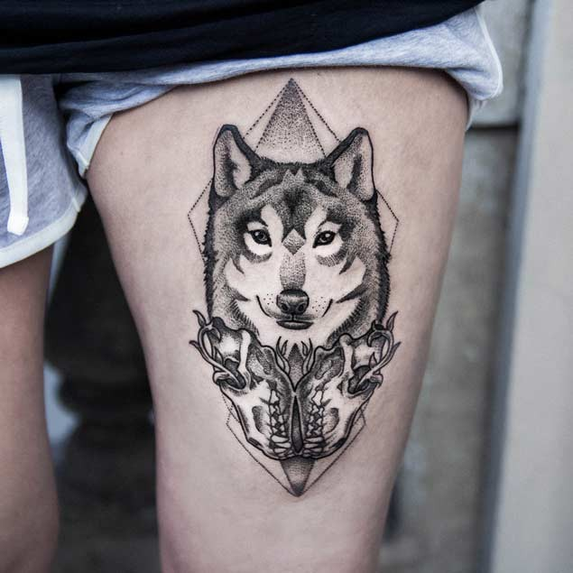 Awesome black and white thigh tattoo of wolf portrait with skulls