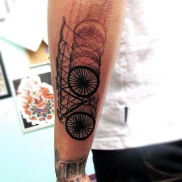 Tatuaje en el antebrazo, bicicleta desenfocada, tinta negra
