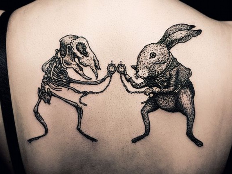 Awesome designed and painted little black ink bunny with skeleton tattoo on upper back