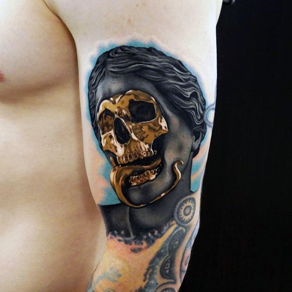 Awesome designed little mystical statue with golden skeleton tattoo on arm