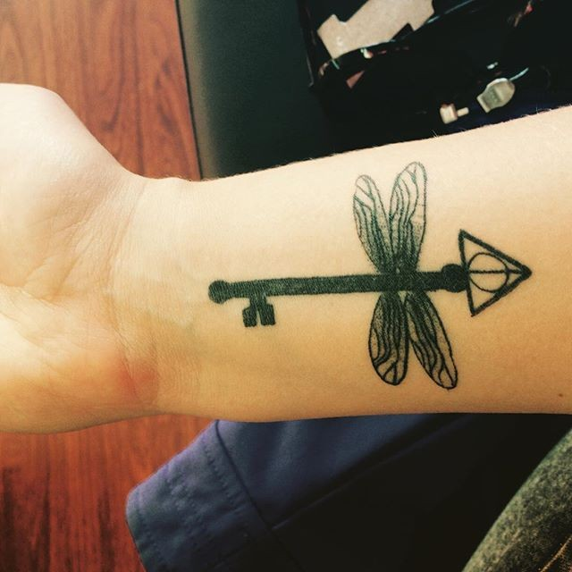 Awesome dragonfly shaped black ink on wrist tattoo of mystic key