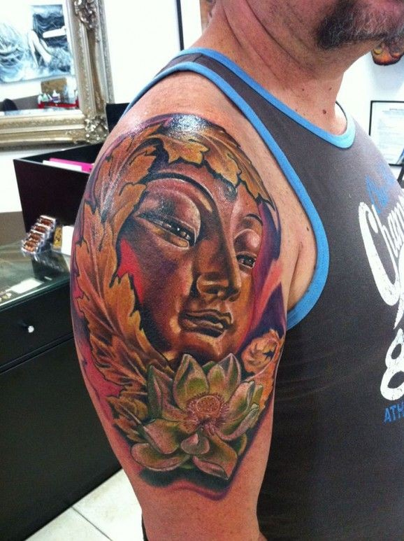 Awesome face of buddha and lotus tattoo by Fabian de Gaillande
