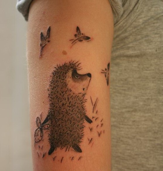 Awesome gray-ink cartoon hedgehog and butterflies tattoo on upper arm