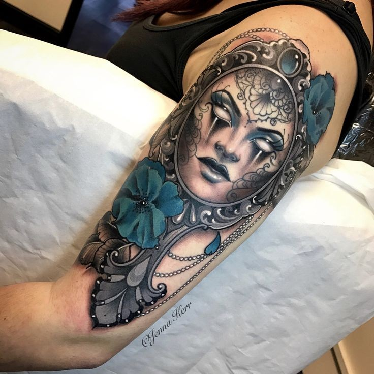 Awesome looking colored upper arm tattoo of mystical mask with flowers painted by Jenna Kerr