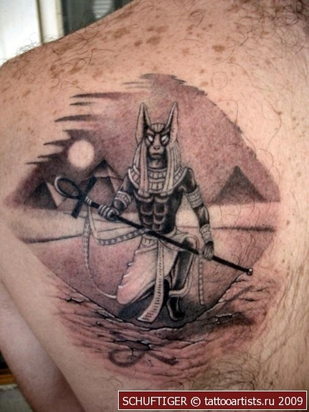 Awesome painted black and white Egypt God tattoo on back with pyramids
