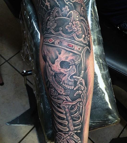 Tatuaje en el brazo, esqueleto de rey en corona preciosa que fuma