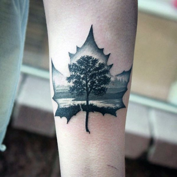 Awesome painted little black ink maple leaf stylized with lonely tree tattoo on arm