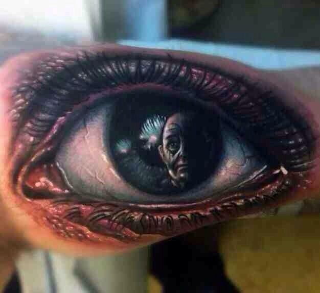 Awesome portrait of a man in human eye tattoo on arm