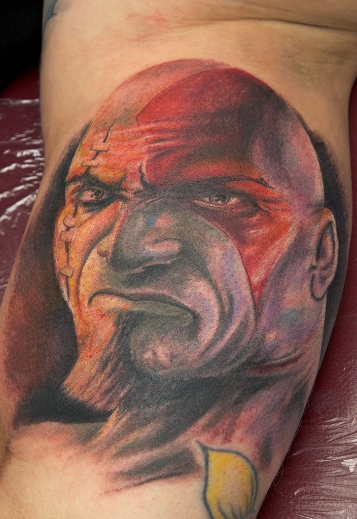 Awesome very detailed colored biceps tattoo of evil barbarian