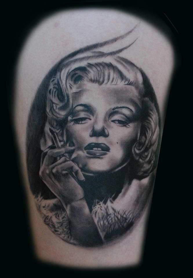Awesome very realistic black and white smoking Merlin Monroe portrait tattoo on thigh