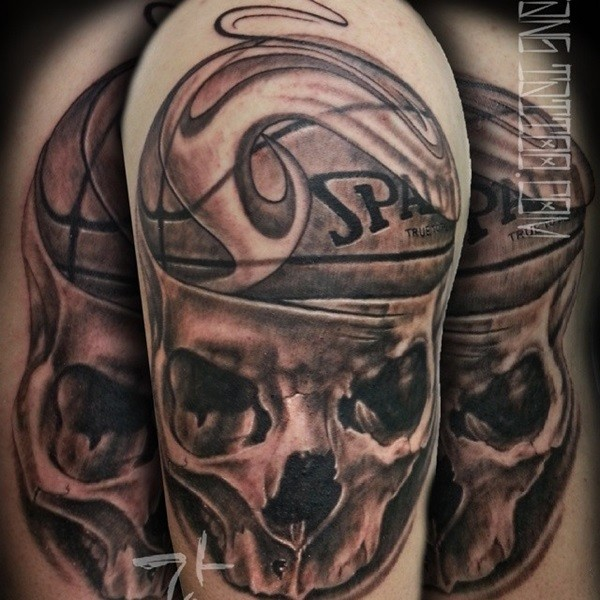 Basketball themed black and gray style shoulder tattoo of human skull and ball