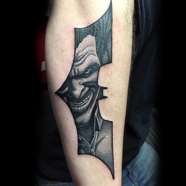 batman symbol shaped black ink arm tattoo stylized with smiling joker. Black Bedroom Furniture Sets. Home Design Ideas