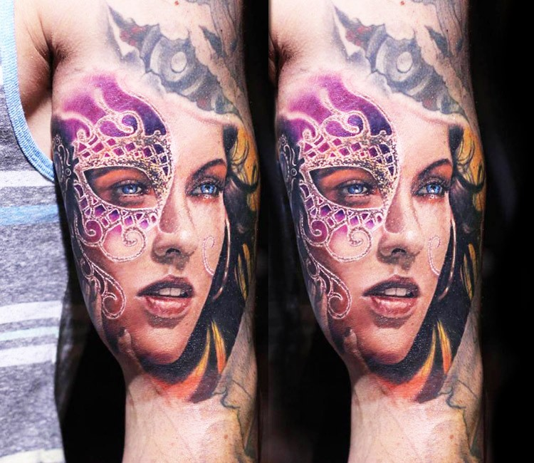 Beautiful colored big detailed biceps tattoo of masked woman portrait