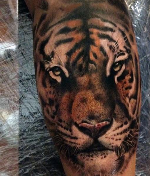 Beautiful colored tiger head tattoo on leg