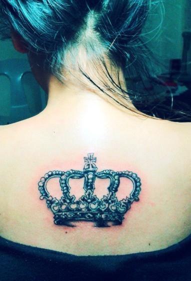 Beautiful crown tattoo on upper back