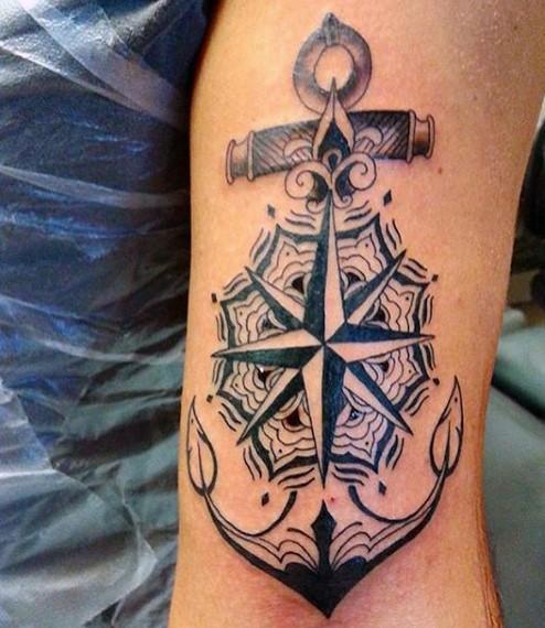 bellissimo disegno nero e bianco nautica con ancora e stella tatuaggio su braccio