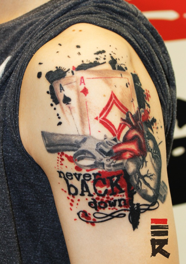 Beautiful gambling themed colored tattoo with gun and playing cards on shoulder