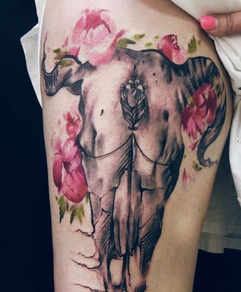 Beautiful looking colored thigh tattoo of mystical animal skull with flowers