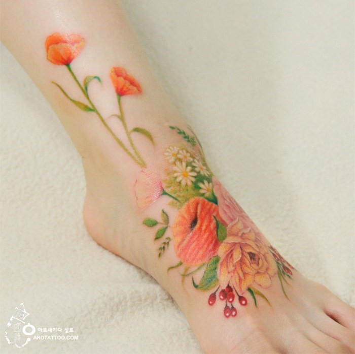Beautiful looking foot tattoo of various flowers