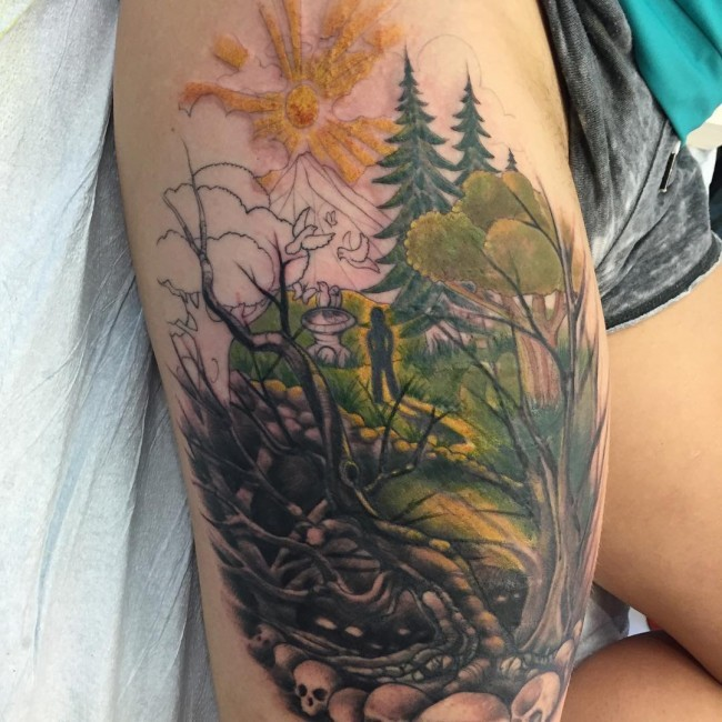 Beautiful looking half colored human figure in dark forest tattoo on thigh stylized with skulls
