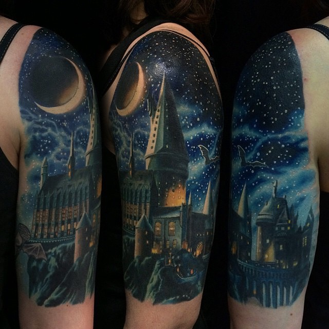 Beautiful looking shoulder tattoo of colored Hogwarts school with bug moon