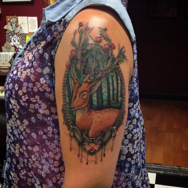 Beautiful natural looking colored deer portrait tattoo on shoulder stylized with berries