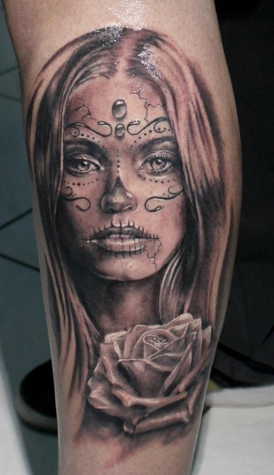 Beautiful santa muerte girl with rose tattoo on leg