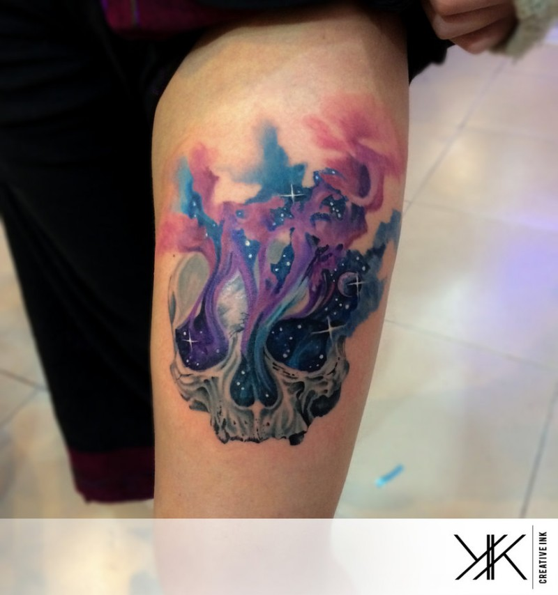 Beautiful space themed colorful on thigh tattoo of skull in colorful fog