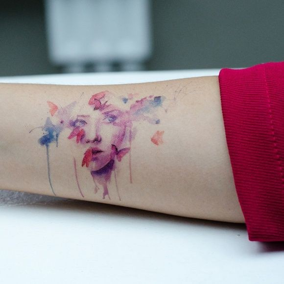 Beautiful watercolor portrait of girl and butterfly forearm tattoo