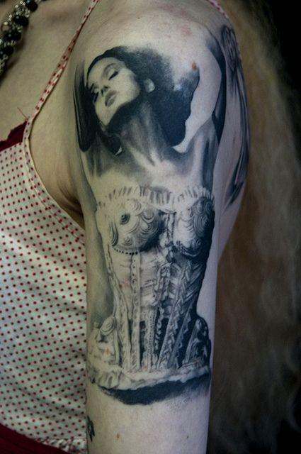 Beautiful women in a corset tattoo on arm