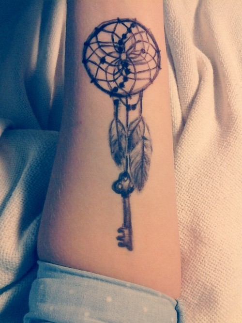 Big American native black ink dream catcher with key tattoo on arm