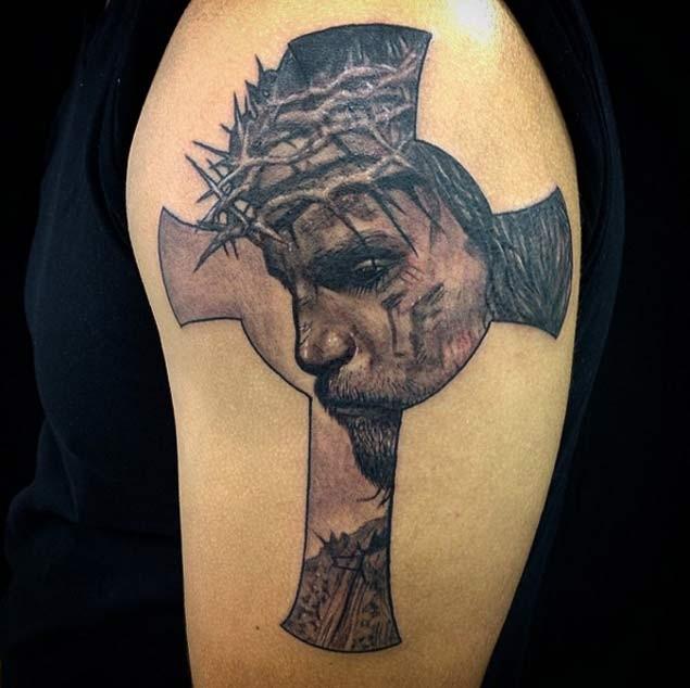 Big antic like cross tattoo on shoulder stylized with detailed sad Jesus portrait