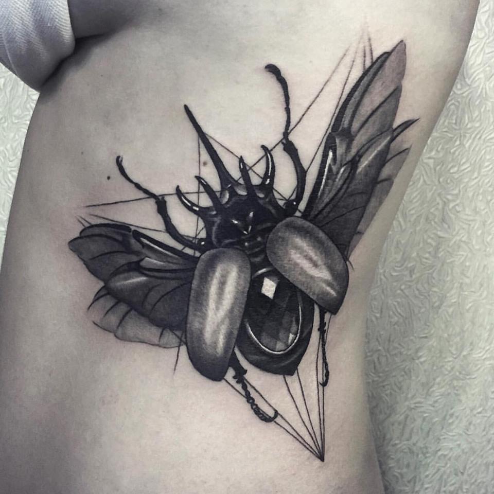 Big black e gray beetle tattoo sul lato