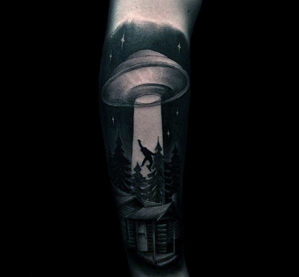 Big black and white alien ship with human and house tattoo on arm