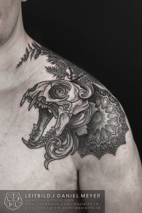 Big black and white animal skull with flowers and leaves tattoo on shoulder