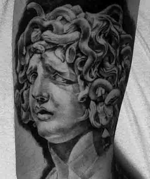 Big black and white antic Medusa statue tattoo on arm