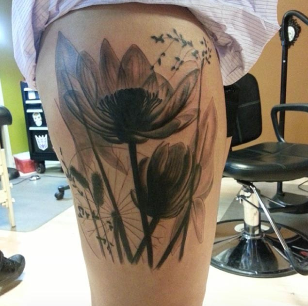 Big black and white beautiful looking thigh tattoo of wildflowers