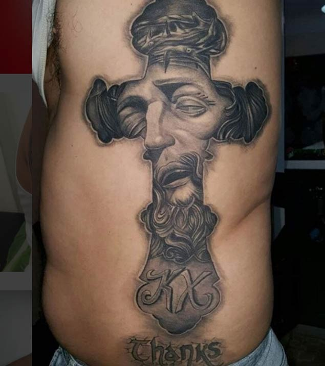 Big black and white cross shaped side tattoo stylized with Jesus face and lettering