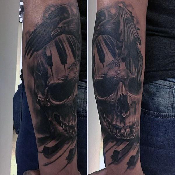 grande nero e bianco dettagliato corvo con cranio tasti del piano tatuaggio avambraccio