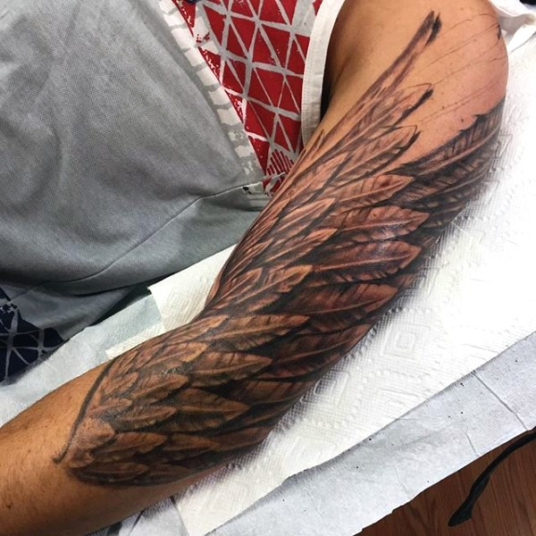 Big black and white detailed wing tattoo on sleeve