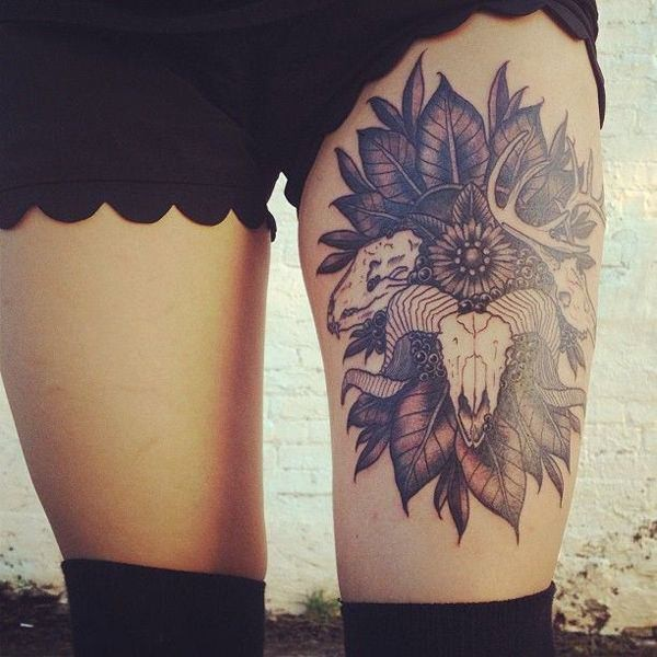 Big black and white flowers with leaves tattoo on thigh combined with various animals skulls