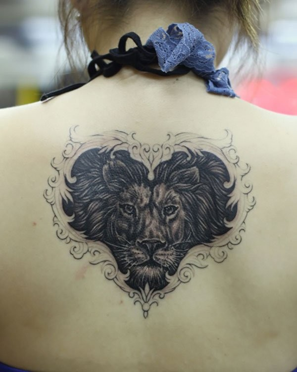 Big black and white heart shaped tattoo on upper back stylized with lion