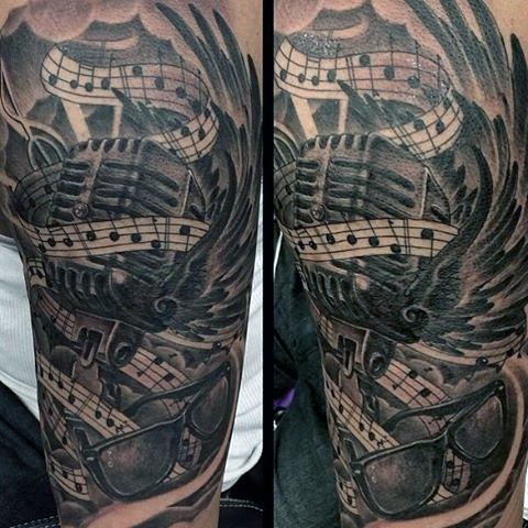 Big black and white microphone with notes and glasses tattoo on arm