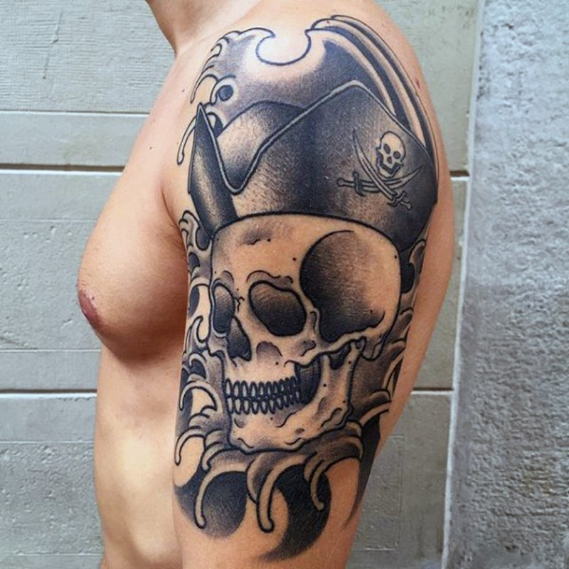 Big black and white pirate skull in hat tattoo on shoulder area