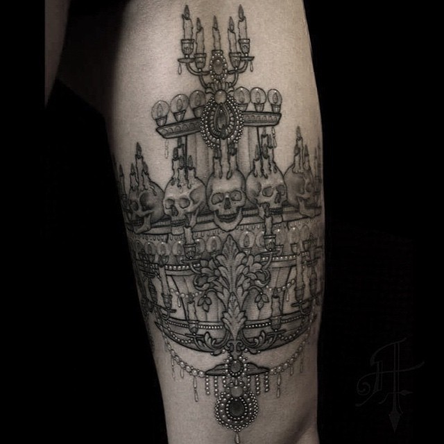 BIg black ink arm tattoo of big demonic candles with skulls
